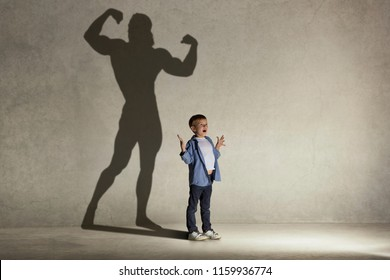 The little boy dreaming about athletic bodybuilder figure with muscles. Childhood and dream concept. Conceptual image with boy and shadow of fit athlete on the studio wall
