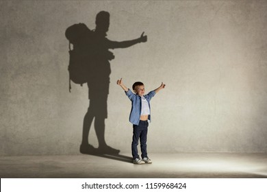 The little boy dreaming about tourism and adventure. Childhood and dream concept. Conceptual image with boy and shadow of tourist on the studio wall