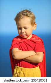 little boy dressed as superhero on the coast