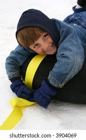 little boy dressed in winter gear on a black tube with a darling smile