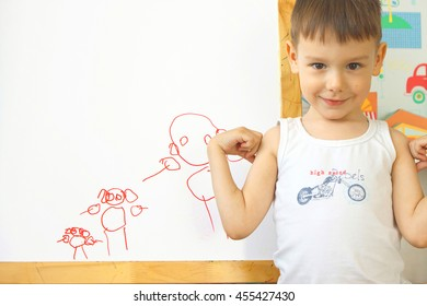 The little boy drew a family with a red marker on the board