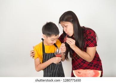 Little boy drink fruit juice watermelon with mother