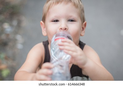 Little boy drink water from bottle , outdoor
