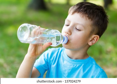 Little boy drink water, outdoor