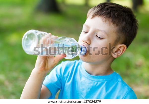 Little boy drink water, outdoor