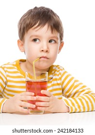 Little boy is drinking apple juice using straw, isolated over white