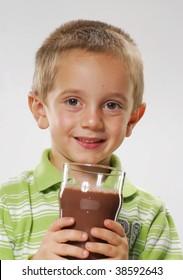 Little boy drinking chocolate drink,happy boy drinking milk,