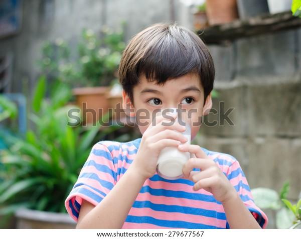 小男孩喝牛奶在公園復古色彩風格