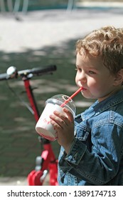 The little boy is drinking a milkshake from a straw in the park