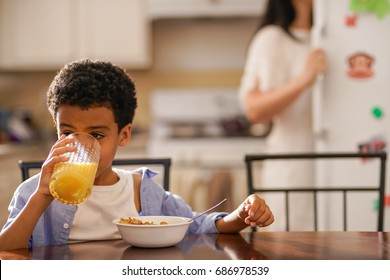 little boy drinking orange juice at breakfast with mother in background