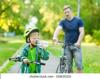 Little boy drinking water by the bike.
