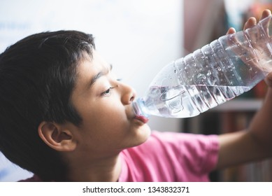 Little boy drinking water in the room with happy face