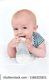 The little boy drinks milk from a bottle.