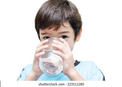 little boy drinks water from a glass