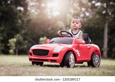 Little boy driving big toy car in park
