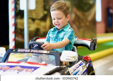 Little boy driving toy car on the traffic playground