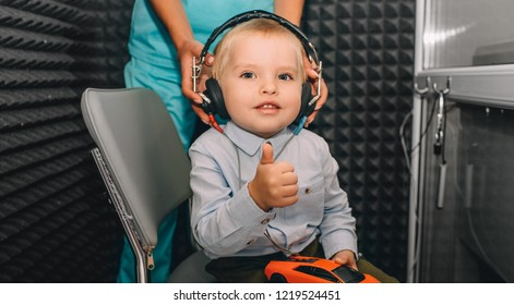 little boy during the hearing exam, showing thumbs up at the audiologist's office. audiogram, children ear exam