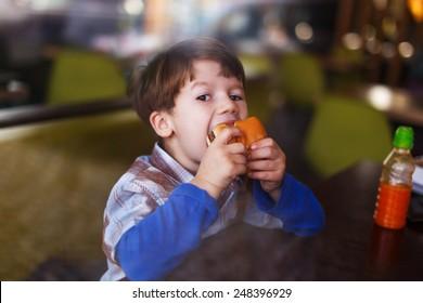 Little boy eat hamburger behind glass in fast food restaurant