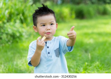 Little boy eat with his snack and thumb up