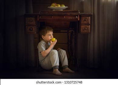 Little boy is eating apple sitting under the retro sewing machine. Image with selective focus and toning.