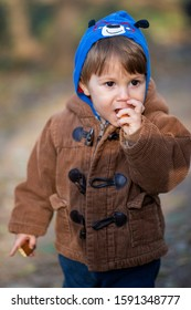 little boy eating biscuit in park