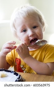 A little boy is eating a cake and all messed up