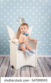 Little boy eating cake in a chair in her first birthday. Funny image of a child in the crown.