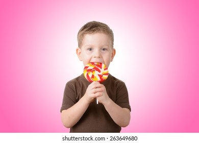Little boy eating candy on a stick closeup