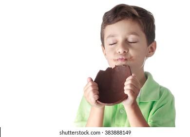 Little boy eating chocolate easter egg on white background
