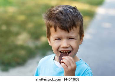 Little boy eating chocolate, outdoor