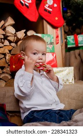 Little boy eating Christmas candy surrounded by gifts