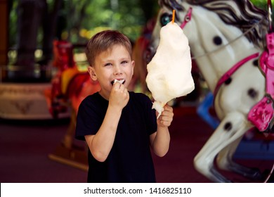 Little boy eating cotton candy at amusement park. The boy holding a candyfloss in his hand and looking into the camera.