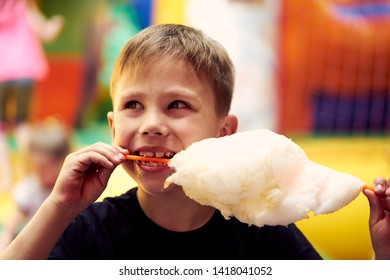 Little boy eating cotton candy at amusement park. The boy holding a candyfloss in his hand.