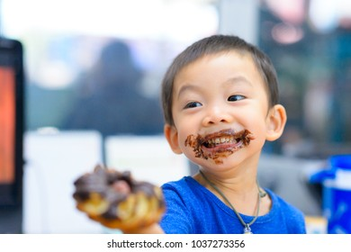 Little boy eating donut chocolate. Cute happy boy smeared with chocolate around his mouth. Child concept.