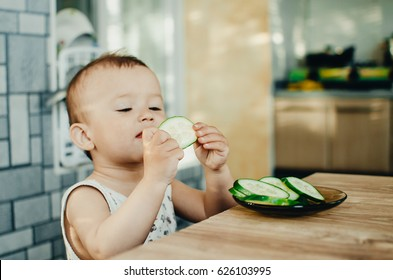 Little boy eating a fresh sliced cucumber in the kitchen