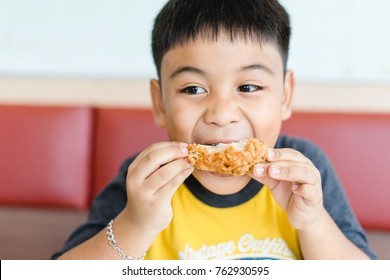 Little boy eating fried chicken in fast food restaurant.