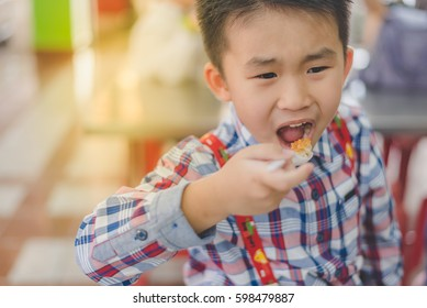 Little Boy eating fried fish.