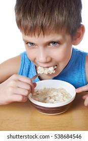 Little boy eating porridge at the table isolated white