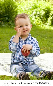 little boy eating red apple in the park