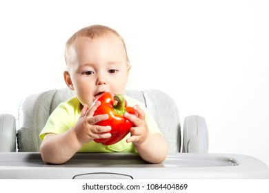 Little boy eating a red paprika sitting in a chair.