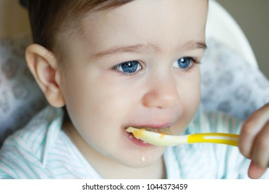 A little boy is eating soup. To the child 1 year. Children's food.