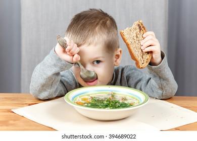 Little boy eating soup for dinner