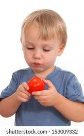 Little boy eating a tomato