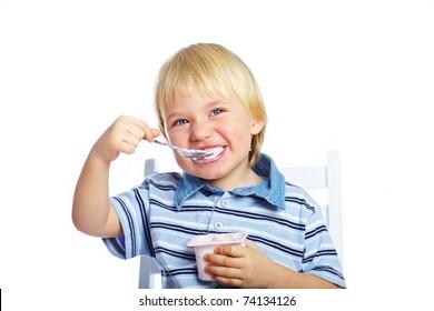 Little boy eating yogurt isolated on white background