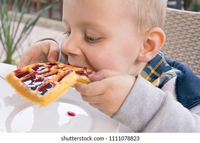 A little boy eats dessert (Belgian waffles with jam) in a cafe.