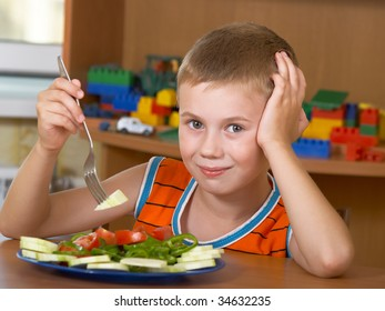 The little boy eats fresh salad on the table