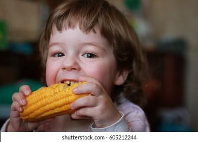 little boy eats greedily biting corn grain