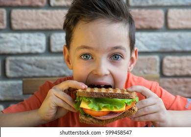 Der kleine Junge isst ein riesiges Brot.