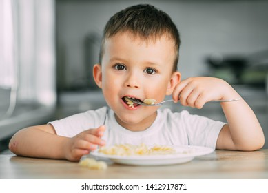 a little boy eats pasta in the form of a spiral in the afternoon in the kitchen on their own very appetizing