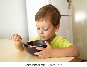 The little boy eats porridge oatmeal
